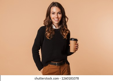 Smiling young woman wearing sweater standing isolated over beige background, holding takeaway coffee cup