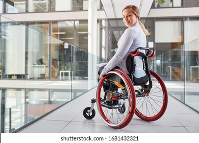 Smiling young woman in wheelchair in business company for inclusion concept