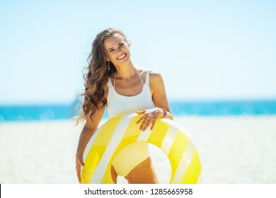 smiling young woman in white beachwear with yellow inflatable lifebuoy on the beach. getting vitamin D after long winter months. сaucasian woman with long brunette hair 30 something years old.