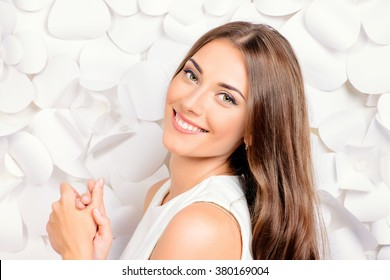 Smiling young woman in white dress posing by the background of white paper flowers. Beauty, fashion. Healthy teeth. Cosmetics.