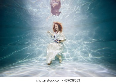 Smiling young woman in white dress poses in swimming pool underwater.