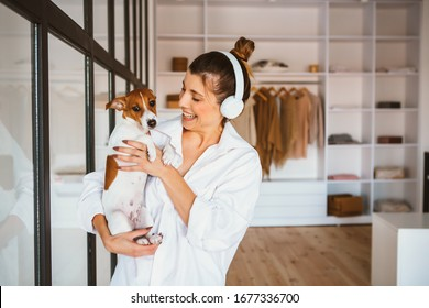 Smiling young woman in white shirt enjoying good day and posing with her pet at home and listen music.