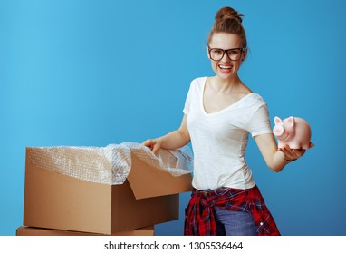 smiling young woman in white t-shirt showing piggybank on blue background. Don't overspend on packing supplies. Economy way to relocation.