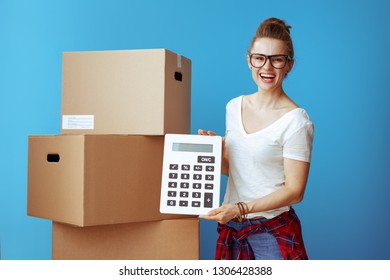 smiling young woman in white t-shirt near cardboard box showing calculator on blue background. Moving on budget. obtain quotes from professional movers.