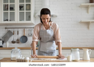 Smiling young woman work with wooden roller pin making sweet pie or pastry dough in kitchen, happy millennial female loving wife cooking in apron preparing family dinner or dessert baking buns
