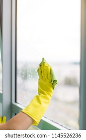 Smiling young woman worker cleaning soap suds on glass window with squeegee and rag