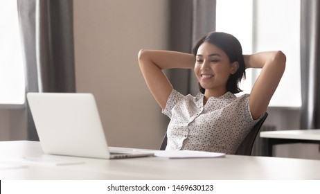 Smiling young woman worker sit in chair hands over head take break from work thinking or dreaming, happy female employee stretch at workplace look at laptop screen watching video online