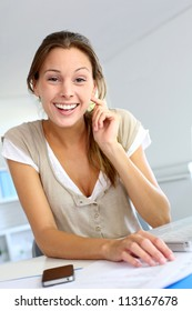 Smiling young woman working from home on laptop