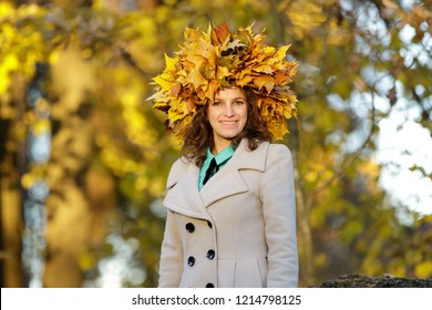 Smiling young woman with wreath of golden maple leaves on her head.