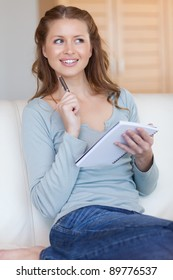 Smiling young woman writing down notes