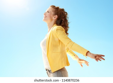 smiling young woman in yellow jacket rejoicing against blue sky