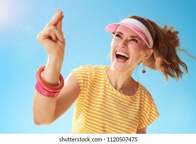 smiling young woman in yellow shirt against blue sky fingers snapping