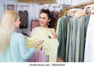 Smiling young women 35s shopping at the clothing store