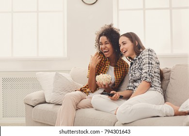 Smiling young women relaxing and watching TV at home, female friends having rest after hard week, copy space