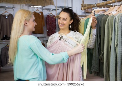 Smiling young women shopping at the apparel store
