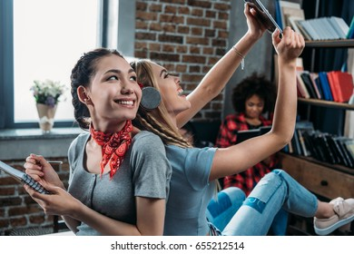 Smiling young women sitting back to back while writing in notebook and using digital tablet