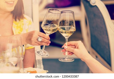 Smiling young women sitting in restaurants and touching the glasses with each other