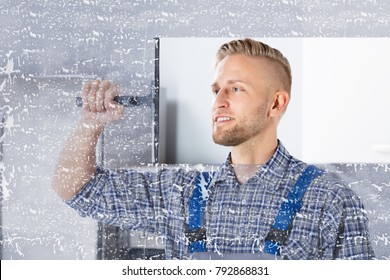 Smiling Young Worker Cleaning Glass Window With Squeegee In Kitchen