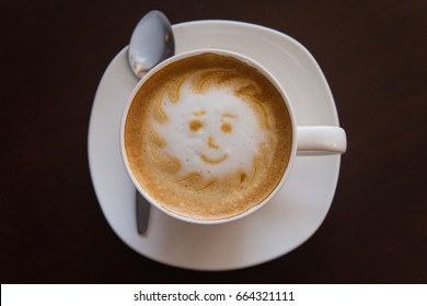 smille boy latte art,A cup of coffee late art with space on wood background,