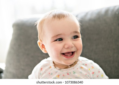 A smilling baby on a grey couch
