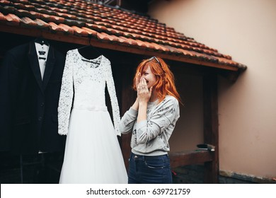 The smilling bride stands near dress and costume