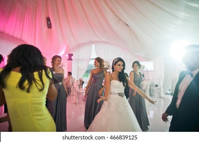 The smilling bridesmaids and bride  dancing on the dancefloor