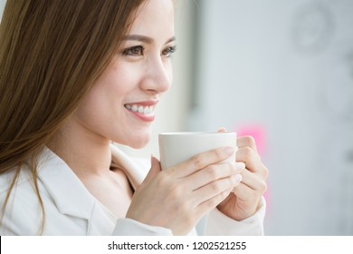 Smilling, Business woman holding white cup of Hot coffee in modern office room, Business woman typing on computer sitting at white table at headquarters