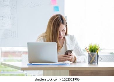 Smilling, Business woman using the mobile phone in modern office room, business woman typing on computer sitting at white table at headquarters