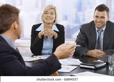 Smilling businesspeople at meeting table in office.?