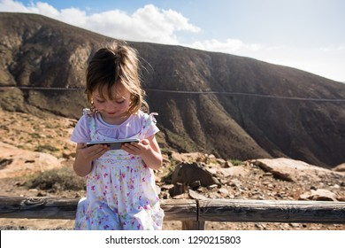 Smilling little girl playing games on smartphone in the mountains
