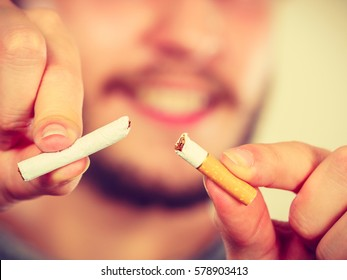 Smilling man breake down cigarette. Winning with addicted nicotine problems, stop smoking. Quitting from addiction concept.