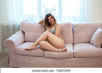 smilling plus size model in lingerie sit on pink couch