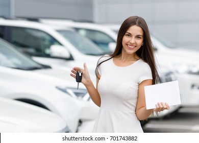 Smilling woman with keys and agreement on background of car dealership