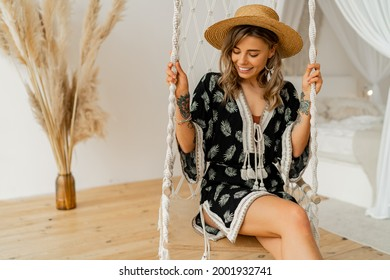 Smilling young woman in boho dress posing in stylish bedroom.  Sraw hat, boho feather drop earrings . Lady sitting on hanging swing.