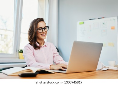 Smilling young woman working in office with laptop