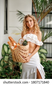 Smilng curly hair caucasian woman in white top and skirt, hold in hands wicker bag with fruits ang baguete bread, look at the camera and smiing while stand outdoor