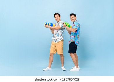 Smilng happy Asian male friends playing with water guns in blue isolated background for Songkran festival in Thailand and southeast Asia