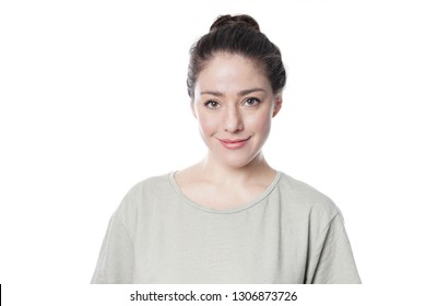 smilng young woman in her 20s with natural make-up and brunette hair bun isolated on white background