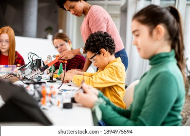 Smily African American female science teacher with group of kids programming electric toys and robots at robotics classroom