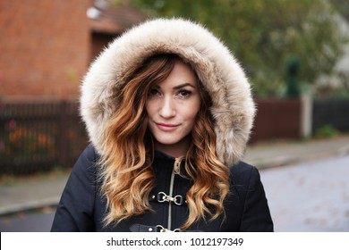 smirking young woman wearing winter coat with fake fur hood outdoors on suburban street in Germany