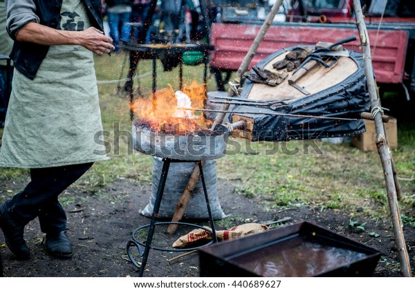 smith warms iron. Master blacksmith heats steel part in the fire. Smith blows the coals and warm metal. Bellows.