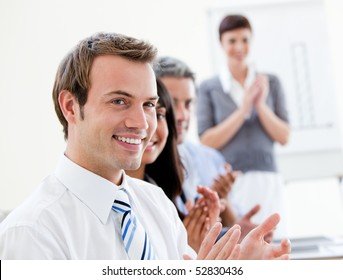 Smling business people applauding a good presentation in the office