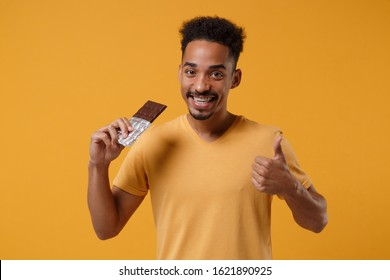 Smling young african american guy in casual t-shirt posing isolated on yellow orange background studio portrait. People lifestyle concept. Mock up copy space. Showing thumb up, holding chocolate bar