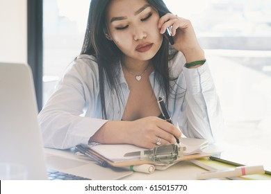 SMM specialist is making business calls by smartphone from the home office. Beautiful model look asian woman is sitting at the table with a laptop on it while talking by a cellphone.