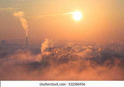 Smog, fog and air pollution over a city during a winter sunrise.