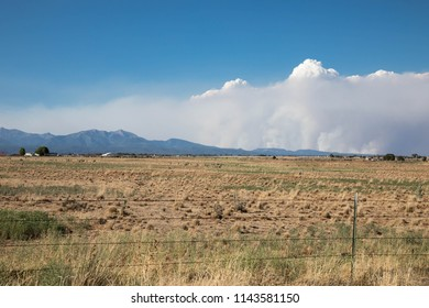 Smoke from the 416 forest fire over a dry grass field in Durango, Colorado