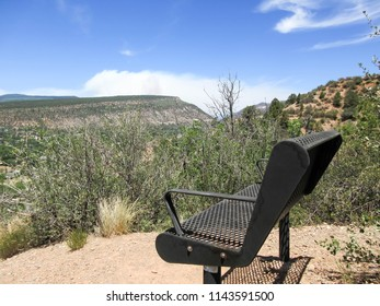 Smoke from the 416 forest fire over a bench on the Rim trail in Durango, Colorado