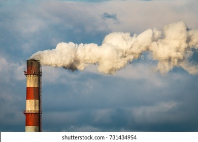 smoke, air emissions from an industrial pipe on a blue sky background