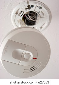 Smoke alarm dangling from ceiling
