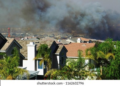 Smoke from an approaching wildfire can be seen hanging over a housing development in Southern California.
